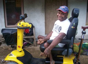 A smiling Issac sits atop his mobility scooter in Vanuatu.