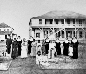 Daughters of leprosy patients at Kaka'ako Branch Hospital, with Walter Murray Gibson and the Sisters of St Francis. These children were separated from their families when their parents were removed to Molokai for isolation. (Utah State Historical Society)
